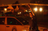 (DENVER, Colo. August 19, 2004)  A Denver police officer raises crime scene tape to allow a police...