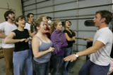 Zander Meisner, (cq), right, leads some of the cast in a song during rehearsals of the musical...