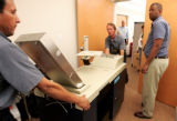 Workers remove a broken  Optech 400C High Speed Optical scanner at the Denver Election Commission...