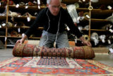 Robert Mann owner of Robert Mann Oriental Rugs, 2540 Walnut St., re-rolls a northwestern persian...