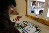 Lynn Rapp (cq, far left) unboxes a cake with the likeness of USMC Cpl. Brett Lee Lundstrom as she...