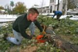 DLM00091   Skip Thurman, left, uses one of his chain-saws to his neighbor Jason Shimkos, right,...