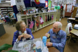 School volunteers Carl and Judy Herbet have lunch in the third-graders' classroom, where their...