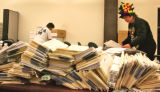 Election Commission workers separate ballots before they are counted on Sunday afternoon, November...