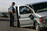 Two Adams County Sheriff's deputies look over a van that was shot at by police as police...