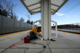 Jerry Heffernan, cq of Skyline Steel, makes last minute fitting repairs to a pedestrian platform...