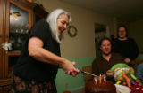 Alice Richardson (cq), left, lights the candles on a birthday cake for her son-in-law Paul...