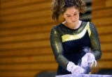 Green Mountain High School sophomore gymnast Kelly Stone (cq), 15, chalks her hands before...