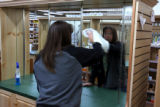 Kristina Schneider, store employee, cleans mirrors in the Cottage Spa, health and beauty area of...