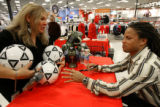 Sherri Wakehouse, cq, (left) delicately drops a soccer ball on the table for Major League Soccer...