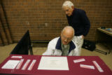 (Timeshot: 06: 19)  Election judges Neil Knutson (cq), front,  and Kenneth Blancett (Cq) prepare a...