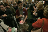 Dominic Atencio (cq) with America Votes hands out treats to voters  who have waited 2-3 hours to...