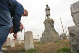 (DLM1262) -  Chuck Counts puts a flag in the ground in front of the grave of one of the many...