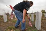(DLM1431) -  Ray Thal puts a flag in the ground in front of the grave of one of the many veterans...