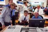 Rocky Mountain News Editor John Temple, seated center, and Database Reporter Burt Hubbard, seated...