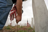 (DLM1493) -  Ray Thal puts a flag in the ground in front of the grave of one of the many veterans...