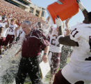 TXBRY501 - Texas A&M head football coach Dennis Franchione is dunked with water by offensive...
