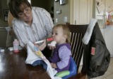 Grandma, Candice Dotson gives her granddaughter Savannah, 16 months, some medicine at her son and...