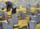 MJM071  Geri Tolen (cq), 75, of Denver places a flag near a grave of a veteran Friday morning at...