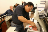 Nelson Chang, cq, optical scanner technician, cleans the machines roller as counting of absentee...
