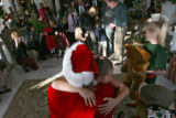 (DLM1557) -  Cassidy Bucholz, 8, gives a hug to Santa Claus during the annual lighting of the tree...