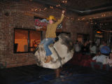 Tracy Shankle gives the mechanical bull a shot at the Urban Cowboy benefit for CityWILD (DAHLIA...