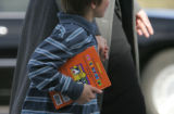 JPM056 A unidentified young boy carries a book into Colorado Community Church on Wednesday, Nov....