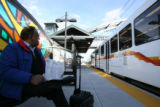 (DLM5922) -  Rajesh Dham, of Englewood, waits at the Orchard Road Station for a F-Line train to...
