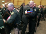 (left) Deputy Jim Valbert is hugged by Helen Stoddard- Keyes (cq) and Golden Police officer Dave...