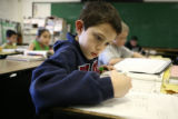 Dupont Elementary School fourth grader Darrian Hale, cq, 9, works on a spelling exercise during...