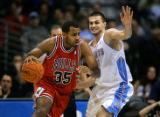 The Chicago Bulls Malik Allen (#35) tries to drive past the Denver Nuggets Linas Kleiza (#43)...