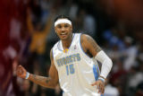The Denver Nuggets Carmelo Anthony (#15) celebrates a dunk by teammate J.R. Smith (not pictured)...