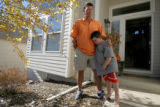 Alan Cockrell, cq, the Rockies' newest hitting coach, stands in the front yard with his son Beau,...