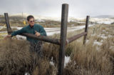 Orlyn Bell (cq)  surveys weeds along a metal fence along the road leading to a pad site on their...