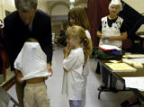 (DENVER, Colo., Aug. 10, 2004)   John Walsh helps his son, John, 4, put his shirt on inside out...