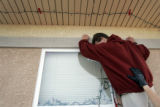 A resident of the El Pueblo Adolescent Treatment Community in Pueblo, Colorado, puts lights up on...