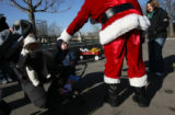 Santa greets Lucas Matthes,2, with his father Christian holding daughter Lisa, 5 months, left,...