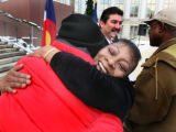 Marshelle Oliver hugs Brian Fiore after speaking on the steps of the City and County Building,...