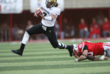 (DLM0894) -  In the second quarter University of Colorado quarterback Bernard Jackson scrambles to...