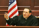 Judge Carlos Samour points his finger like a gun as he talks about how Reynolds used his car like...