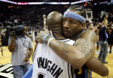 Denver Nuggets' Allen Iverson, right, hugs San Antonio Spurs'  Jacque Vaughn, left, as they leave...