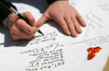 A CSU student writes a message on a banner for Virginia Tech at a memorial for victims of the...