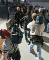 Federal police officers escort former Qwest CEO Joe Nacchio through a pack of photographers from...