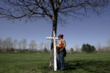 Sommer McGuire (cq), 29, signs a large cross set up in the free speech area of Clements Park in...