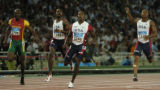 American sprinter Shawn Crawford, #3246, looks at the board for his time of 19.79 seconds in the...