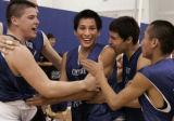 Team mates mob Coree Straight Head  (center) after he dropped a fade away shot in the second OT of...