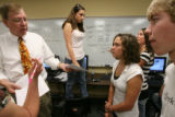 DLM0369  Journalism teacher Jack Kennedy, left, helps direct his students as the work to put the...