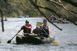 Don Dowling (left) and Sean Davis paddle a two person cataraft to a pull out to empty trash  at...