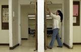 (DENVER, CO., PHOTO SHOT ON Aug 9, 2004) Rima Barakat-Sinclair puts a  sign on a door to a sunday...