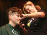 Sean Moyle (cq), 14, has his head shaved by volunteer Maggie Young (cq) along with over  20...